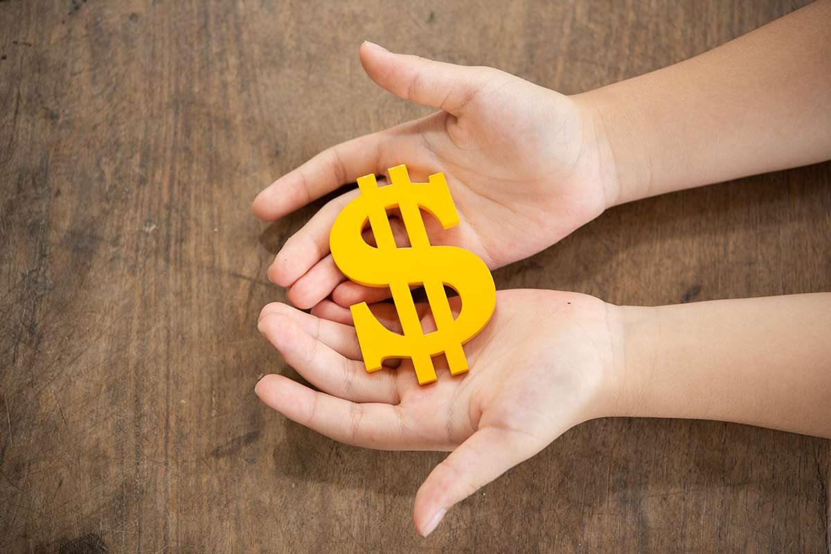 The yellow dollar symbol on hands child for the investment or saving of people with differences diversity for insurance, education, safety life for good and stable in future of family