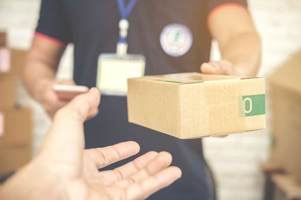 delivery man smiling and holding a cardboard box