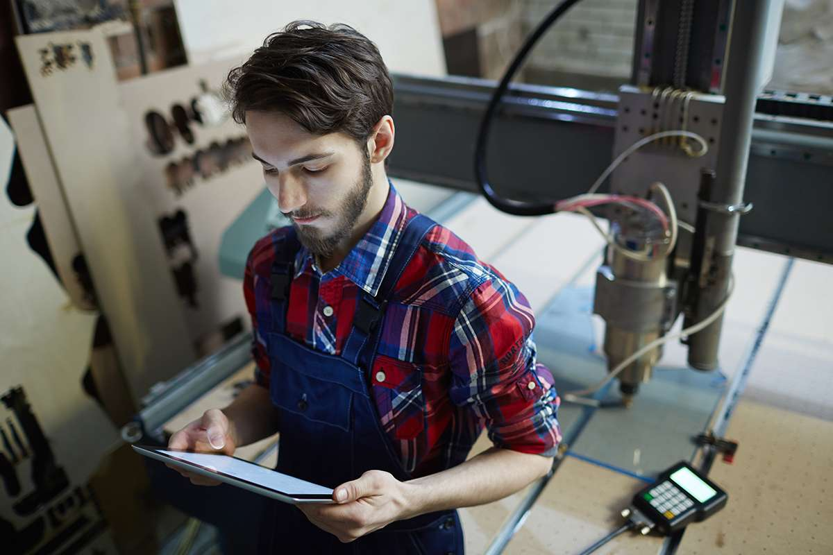 Professional engineer with touchpad standing by lathe-machine